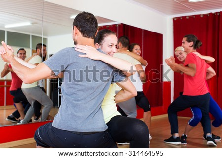 Smiling adults dancing bachata together in dance class - stock photo