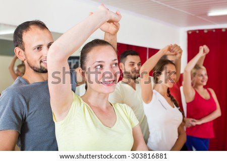 Smiling adults dancing the bachata together at dance studio  - stock photo