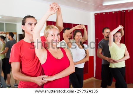 Smiling adults dancing the bachata together in dance studio