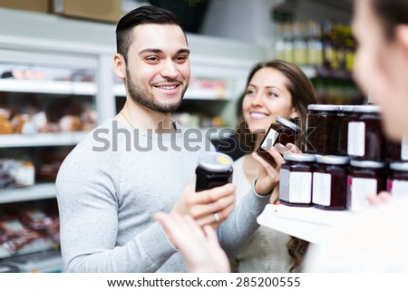 Smiling adults people choosing tinned food at supermarket - stock photo