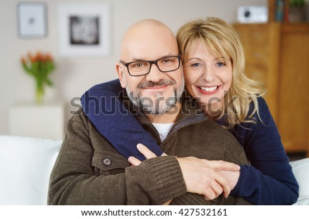 Smiling affectionate middle-aged couple posing in an intimate embrace on the sofa at home looking at the camera with happy smiles, head and shoulders portrait