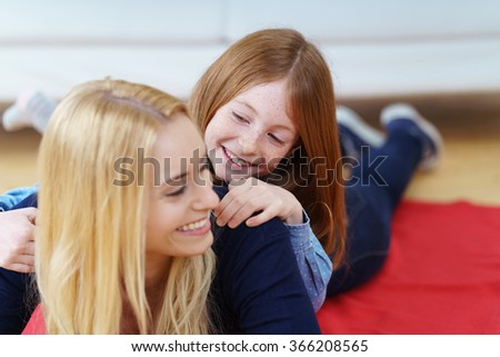 Smiling affectionate young mother and daughter lying on a red rug in the living room playing together with the girl riding on her back with a happy smile - stock photo