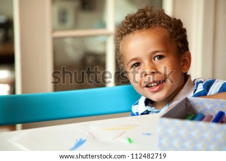 Smiling African American boy sitting on a chair and getting ready for his lesson - stock photo