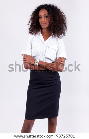 Smiling african american business woman with folded arms - stock photo