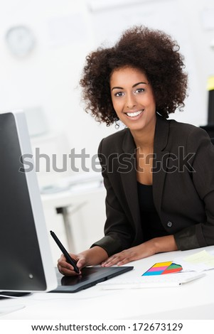 Smiling African American businesswoman at her desk using a tablet an stylus to draw or enter data on her desktop computer - stock photo