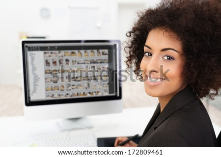 Smiling African American businesswoman editing photographs visible on her computer screen as she turns to smile at the camera - stock photo