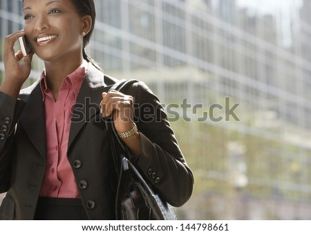 Smiling African American businesswoman using mobile phone against building - stock photo