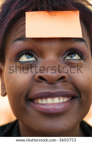 Smiling African American businesswoman with post it reminder note on forehead - focus on eyes - stock photo