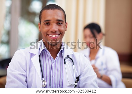 Smiling african-american doctor making with colleagues behind - stock photo