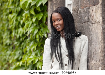 Smiling African American female standing in front of stone wall - stock photo