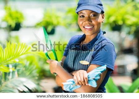 smiling african american gardener holding garden tool - stock photo