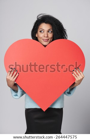 Smiling african american girl holding big red heart shape, and looking away - stock photo