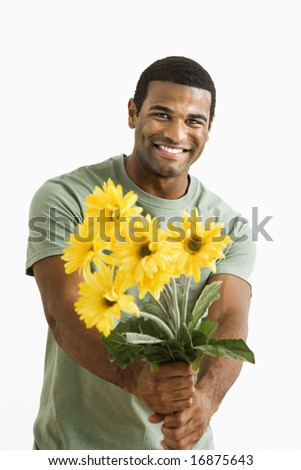 Smiling African American male holding out bouquet of yellow flowers to unseen person. - stock photo