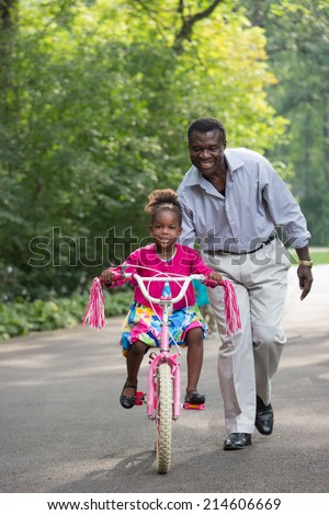 Smiling African American Man Helping Little Girl Biking Outdoor, grandpa and grand daughter - stock photo