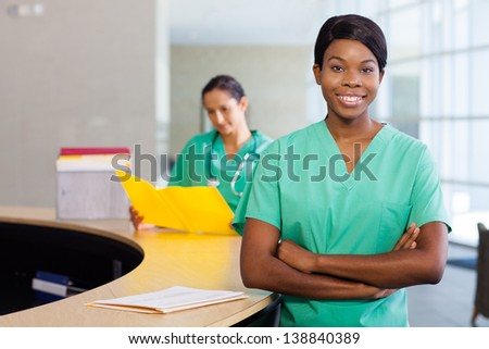 Smiling African American nurse at hospital work station lit brightly and arms folded.  Second female medical professional in background. - stock photo
