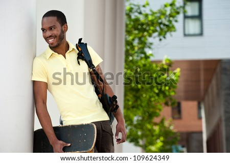 Smiling African American student leaning against a campus wall with skateboard and bag over his shoulder. - stock photo