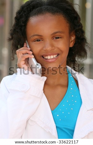Smiling African American Teenager Girl on Cell Phone, texting or dialing - stock photo