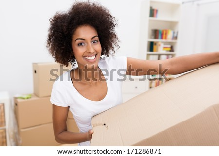 Smiling African American woman in a new home carrying a cardboard packing carton - stock photo
