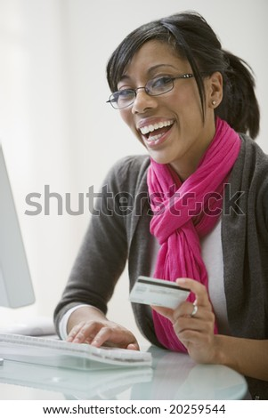 Smiling African American woman shopping on-line with credit card and computer - stock photo