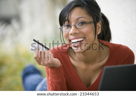 Smiling African American woman shopping on-line with credit card and laptop