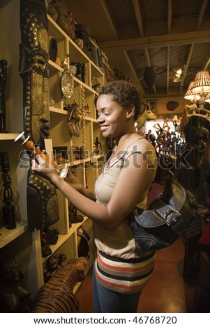 Smiling African American woman standing and looking at a candlestick or vase in a retail display. Vertical format. - stock photo