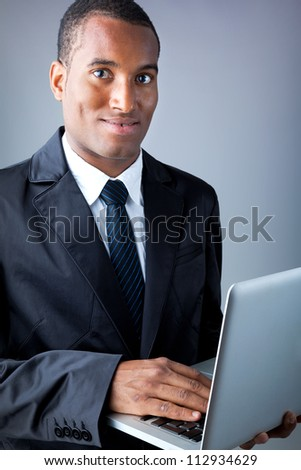 Smiling African American young businessman with laptop