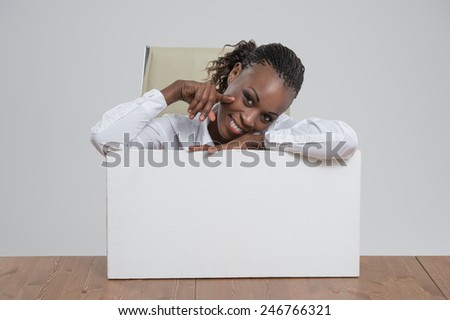 Smiling African Business woman portrait sitting at workplace with blank white board on gray isolated background Female model with long hair. - stock photo