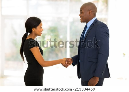 smiling african businessman handshaking with young businesswoman in office - stock photo