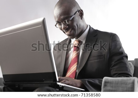 Smiling african businessman sitting in front of a laptop - stock photo