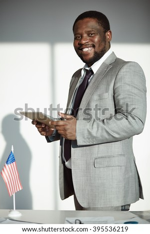 Smiling African businessman standing with touchpad at office
