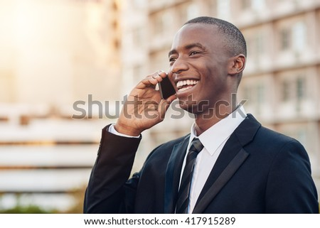 Smiling African businessman talking on his mobile phone in city - stock photo