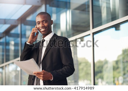 Smiling African businessman using movile phone outside city building - stock photo