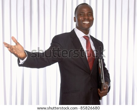 Smiling African businessman welcoming somebody in office surroundings - stock photo