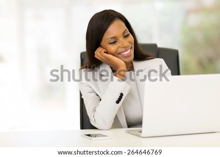 smiling african businesswoman looking at computer screen - stock photo