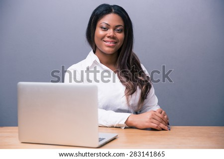 Smiling african businesswoman sitting at the table with laptop over gray background - stock photo