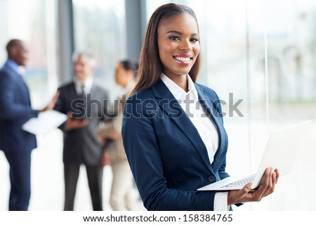 smiling african businesswoman with laptop computer - stock photo