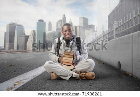 Smiling african student on a city street - stock photo