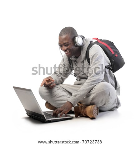 Smiling african student using a laptop - stock photo