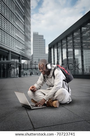 Smiling african student using a laptop with cityscape on the background - stock photo