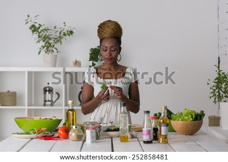 Smiling african woman chopping vegetables for salad at kitchen  - stock photo