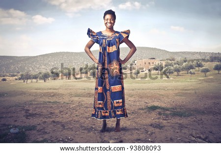 Smiling african woman in traditional clothes on a desert field - stock photo