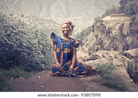Smiling african woman in traditional clothes sitting on a rock - stock photo