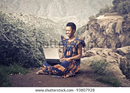 Smiling african woman in traditional clothes sitting on a rock and using a laptop - stock photo