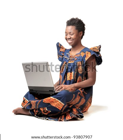 Smiling african woman in traditional clothes using a laptop - stock photo