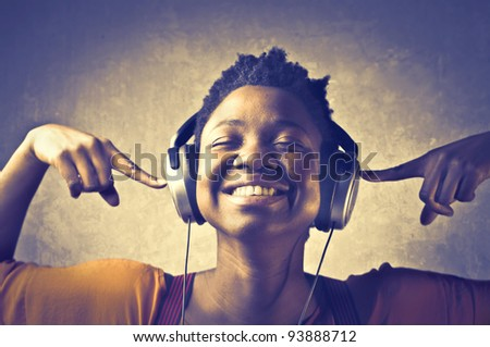 Smiling african woman listening to music - stock photo