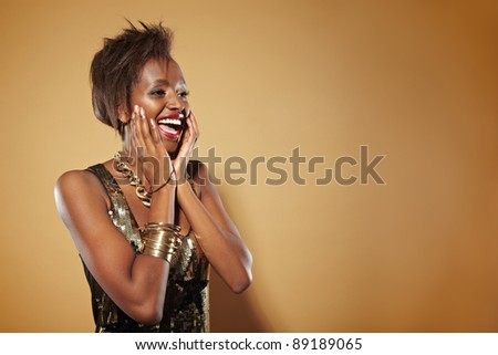 Smiling african woman looking happily surprised with hands on her chin - stock photo