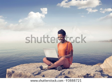 Smiling african woman using a laptop with seascape in the background - stock photo
