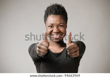 Smiling african woman with thumbs up