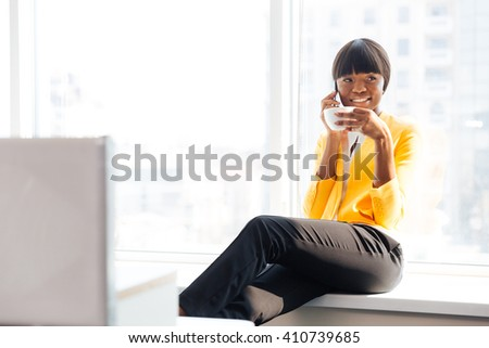 Smiling afro american businesswoman drinking coffee and talking on the phone in office