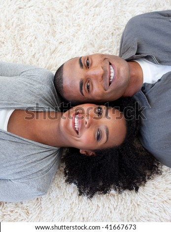 Smiling Afro-American couple lying on the floor at home - stock photo